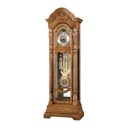 Howard Miller - Howard Miller Nicolette Grandfather Clock Multicolor - 611048 - Shop for Clocks from Hayneedle.com! The Howard Miller Nicolette Grandfather Clock features a Golden Oak finish on select hardwoods and veneers. This floor clock offers a graceful bonnet pediment with book-matched olive ash burl and a decorative shell and vine overlay. An astrological blue moon phase sets off the polished brass dial featuring cast corners center ornaments a silver chapter ring with applied brass Arabic numerals and a Ambassador Collection inscription. The polished-brass pendulum includes a center disk that is complementary to both the dial and weights. The illuminated case and mirrored back highlight the weights and pendulum.The multi-tiered base features a decorative cutout with a wrap-around embossed molding. Intricate carvings above the reeded columns draw attention to the dial. Crystal-cut grooved glass enhances the front lower door with beveled glass on the lower side panels. Removable fret-cut top side panels allow easy access to the movement which is a cable-driven triple-chime Kieninger movement with an automatic nighttime chime shut-off option. This clock also features a locking door for added security. Adjustable levelers under all corners level the clock on uneven or carpeted floors.This clock comes complete with a brass plate that's ready for engraving with your personal message. The plate measures 1H x 3W inches and has double-sided tape on the back for easy mounting to the clock.About Howard MillerBeginning in the 1920's Howard Miller clocks have impressed all who see them with superior quality and design. Howard Miller wall floor and mantel clocks are crafted to last for generations and to perfectly accent your home.The company's founder Howard C. Miller began manufacturing wall and mantel clocks in Michigan. Evolving to encompass cabinet making and other furniture design - all renowned for quality and style - the Howard Miller company proudly stands behind