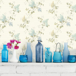 Meadowlark - An eclectic collection of blue glass bottles, candles and milk glass on a painted white brick ledge. Beautiful blue floral wallpaper adds a country chic charm.