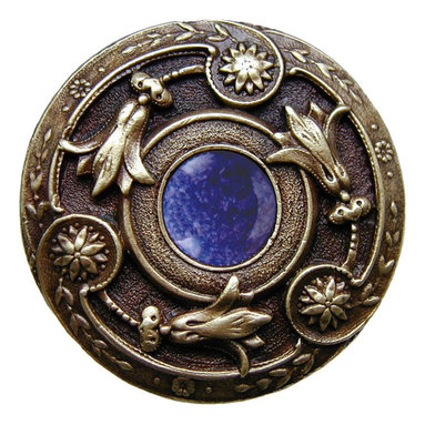 "Inviting Home - Jeweled Lily Knob (antique brass with blue sodalite) - Jeweled Lily Knob in antique brass with blue sodalite semi-precious stone 1-3/8"" diameter Product Specification: Made in the USA. Fine-art foundry hand-pours and hand finished hardware knobs and pulls using Old World methods. Lifetime guaranteed against flaws in craftsmanship. Exceptional clarity of details and depth of relief. All knobs and pulls are hand cast from solid fine pewter or solid bronze. The term antique refers to special methods of treating metal so there is contrast between relief and recessed areas. Knobs and Pulls are lacquered to protect the finish. Alternate finishes are available. Blue Sodalite Semi-Precious stone. Blue Sodalite is a royal blue colored stone that usually has some white or gray-colored streaks. Blue Sodalite looks a bit more crystal-like. It was named by Professor Thomas Thompson who was called in to identify the specimen that was brought from Greenland to Denmark during the time of the Napoleonic wars - he identified it at first as Sodium Aluminum Silicate Chloride. The stone is associated with the Astrological sign Sagittarius and is thought to promote focus clearing mediation and calming of fears."