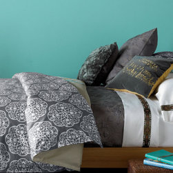 Shangri La Duvet Set -Reversible - Double décor options, double happiness. The front of our Shangri-La duvet set shows our dramatic, oversized medallion motif printed in turquoise, yellow ochre and storm grey on a white and pebble background. Look closely for a bird, a bee and flowers embroidered in coral. On the reverse, a pattern of white medallions stands like a screen set against storm grey Himalayan slopes. A real karma chameleon.