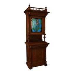 Pre-owned Antique Flemish Oak Stained Glass Buffet - This antique Flemish buffet is a true statement piece for your decor! The real showstopper here is the vibrant stained glass work on the upper door. Hand leaded in shades of lake blue, leaf green, and soft pinks, the floral motif truly reflects the Art Nouveau aesthetic. (Note the stained glass has been enhanced for these photos by placing white paper behind it.)     Dating to 1920, this solid oak buffet features scads of hand work, from the turned spindles at top to the quartet of carved courtiers (and a jester!). Behind the stained glass door, you'll find a shelf for ample storage, while a drawer in the lower cabinet adds functionality. The ornately carved lower door reveals yet more storage space -- perfect for tucking away linens, serving pieces, or the family silver. This buffet represents old world craftsmanship at its finest. Best of all, we'll ship this fine antique Belgian hutch to you free within the continental U.S. and most of Canada!    Overall Condition is Used - Good. Shows normal wear to the finish and miscellaneous nicks, dings, and scratches due to age and use. Both locks have been replaced, there is a dark ring and some staining on the top surface. There is wood separation to the interior bottom floor, on the back at the top, on the lower right side, both the upper and lower panels on the left side, and across the top surface. There has been professional restoration to several panels on the stained glass door.