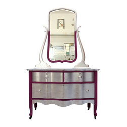 """Pre-owned Orchid and Silver Leaf Cottage Chest & Mirror - A vintage chest with mirror, rehabbed in silver leaf and vibrant orchid. The silver leaf is lightly distressed to reveal the orchid color beneath. The hardware and Cheval mirror are original to the piece. The entire piece has been French waxed for that unmistakable glow and a super resilient surface. Each drawer has been stripped and re-stained.     The seller says: """"We loved the clean lines and serpentine front on this lovely little chest! Why go basic?  We vamped her up with silver leaf and vibrant Orchid!""""    Measures 40""""L x 19""""D x 27 1/2""""T (mirror is an additional 42""""T)"""