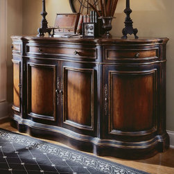 Hooker Furniture - Hooker Furniture Preston Ridge Shaped Buffet - 864-75-900 - Shop for Buffets and Side Boards from Hayneedle.com! Now that's what we call a focal point - the Preston Ridge Shaped Buffet is so stunning it could make anything look great. Seriously - display your Beanie Babies they'll look fantastic on this piece. Four doors three drawers and plenty of style make this a real gem. The contrasting cherry and black rub-through finish gives depth and class to any space. Not available for sale in or delivery to the state of California. About Hooker Furniture Corporation For 83 years Hooker Furniture Corporation has produced high-quality innovative home furnishings that seamlessly combine function and elegance. Today Hooker is one of the nation's premier manufacturers and importers of furniture and seeks to enrich the lives of customers with beautiful trouble-free home furnishings. The Martinsville Virginia based company specializes in lifestyle driven furnishings like entertainment centers home office furniture accent tables and chairs. Construction of Hooker Furniture Hooker Furniture chooses solid woods and select wood veneers over wood frames to construct their high-quality pieces. By using wood veneer pieces can be given a decorative look that can't be achieved with the use of solid wood alone. The veneers add beautiful accents of color and design to the pieces and are placed over engineered wood product for strength. All Hooker wood veneers are made from renewable resources and are located primarily on the flat surfaces of the furniture such as the case tops and sides. Each Hooker furniture piece is finished using up to 30 different steps including 13 steps of hand-sanding and accenting. Physical distressing is done by hand. Pieces receive two to three coats of solid lacquer to create extra depth and add durability to the finish. Each case frame is assembled using strong mortise-and-tenon joints which are then reinforced by mechanical fasteners and glue. On most designs end panels extend to the floor to add strength and stability. Panel-style furniture features strong panel and frame construction to help avoid warping. Your Hooker furniture features finished case interiors to eliminate unsightly raw wood and to help protect items you may store inside drawers or cabinets. Drawer parts are given a urethane or lacquer finish to create smooth action and durability. All drawers use dovetails either English or French for years of problem-free use. Drawer bottoms are constructed from plywood and attached to the plywood drawer sides via the use of hot glue and/or wood glue blocks. Most drawers are full width depth and height to provide the maximum amount of storage space.