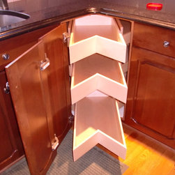 Corner Cabinet Solutions - The Glide-Around corner cabinet unit combines the best of ShelfGenie's Lazy Susan with our pull out shelves.  The center drawers pull out to provide access to the deep part of the cabinet, while each side has additional storage shelves which are accessible when you turn the unit like a Lazy Susan.