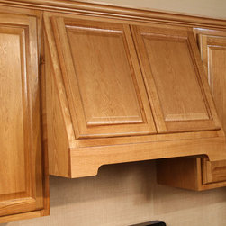 Adrian Oak - A photo of one of our wood hoods in Adrian Oak, our builder grade oak cabinet, made with hardwood face frame, doors, and drawers, and plywood boxes.