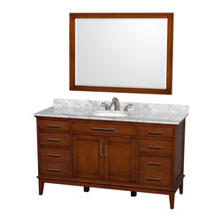 Wyndham Collection - Eco-Friendly Bathroom Vanity with Undermount Oval Sink - Includes matching mirror and white Carrera marble countertop with backsplash. Faucet not included. Engineered to prevent warping and last a lifetime. Porcelain sink. 12-stage wood preparation, sanding, painting and hand-finishing process. Highly water-resistant low V.O.C. sealed finish. Transitional styling. Practical floor-standing design. Deep doweled drawers. Fully-extending under-mount soft-close drawer slides. 8 in. widespread 3-hole faucet mount. Concealed soft-close door hinges. 1.25 in. mirror thickness. Plenty of storage and counter space. Single faucet hole mount. Metal exterior hardware with brushed chrome finish. Made from solid birch hardwood. Light chestnut finish. Backsplash: 60 in. W x 0.75 in. D x 3 in. H. Vanity with countertop: 60 in. W x 22 in. D x 35 in. H. Countertop: 60 in. W x 22 in. D x 0.75 in. H. Mirror: 44 in. W x 33 in. H (40 lbs.). Vanity: 60 in. W x 22 in. D x 35 in. H (185 lbs.). Warranty. Care Instructions. Vanity Installation Instructions. Mirror Installation Instructions. Counter Handling InstructionsBring a feeling of texture and depth to your bath with the gorgeous Hatton vanity series. A contemporary classic for the most discerning of customers. The Wyndham Collection is an entirely unique and innovative bath line. Sure to inspire imitators, the original Wyndham Collection sets new standards for design and construction. Compliments any bathroom.