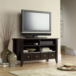 "Sauder - Shoal Creek 47"" TV Stand - With country roots and contemporary soul, Shoal Creek's inviting, casual appearance offers a stylish alternative to the traditional home office. The warm espresso finish is accented with soft nickel-finish bin-style drawer pulls in a distinctive updated shape. Tapered legs and sculpted drawer and door edges confirm this design's country origin. The warm, casual appearance hides a heart built for technology. Each piece is designed with appropriate cable management and correctly dimensioned with storage for everything from files to media. Features: -Holds TVs weighing 70 lbs or less; base must be no larger than 46 5/8 inches.-Two adjustable shelves hold audio/video equipment.-Jamocha Wood finish.-Shoal Creek collection.-Recommended TV Type: Flat.-TV Size Accommodated: 47"".-Finish: Jamocha Wood.-Powder Coated Finish: No.-Gloss Finish: No.-Material: Engineered wood.-Solid Wood Construction: No.-Distressed: No.-Exterior Shelves: Yes.-Drawers: Yes -Number of Drawers: 2.-Drawer Glide Material: Metal runners.-Soft Close Drawer Glides: Yes.-Safety Stop: Yes.-Ball Bearing Glides: Yes.-Joinery Type: T-lock.-Drawer Dividers: No.-Drawer Handle Design: Knobs..-Cabinets: No.-Scratch Resistant: No.-Removable Back Panel: No.-Hardware Finish: Brushed silver.-Casters: No.-Accommodates Fireplace: No.-Lighted: No.-Media Player Storage: Yes.-Media Storage: Yes.-Cable Management: Cable hole.-Remote Control Included: No.-Weight Capacity: 70 lbs.-Swatch Available: Yes.-Commercial Use: No.-Collection: Shoal Creek.-Eco-Friendly: Yes.-Recycled Content: No.-Lift Mechanism: No.-Expandable: No.-TV Swivel Base: No.-Integrated Flat Screen Mount: No.-Non-Toxic: Yes.-Product Care: Wipe with a damp cloth.-Country of Manufacture: United States.Specifications: -ISTA 3A Certified: Yes.-CARB 2 Certified: Yes.-CARB Certified: Yes.-FSC Certified: Yes.-General Conformity Certified: Yes.-EPP Certified: Yes.Dimensions: -Overall Height - Top to Bottom: 26.929"".-Overall Width - Side to Side: 46.85"".-Overall Depth - Front to Back: 18.937"".-Drawer: Yes.-Shelving: Yes.-Cabinet: No.-Legs: Yes.-Overall Product Weight: 99 lbs.Assembly: -Two drawers with metal runners and safety stops feature patented T-lock assembly system.-Assembly Required: Yes.-Tools Needed: Phillips screwdriver and hammer.-Additional Parts Required: No.Warranty: -Product Warranty: 5 Years."