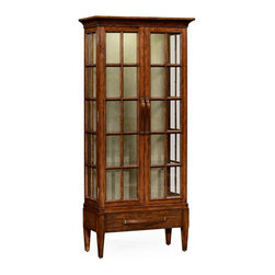 Jonathan Charles - Jonathan Charles Huntingdon Country Farmhouse Walnut China Cabinet - Practical country style planked walnut glazed display cabinet on raised base with internal lighting two doors and adjustable glass shelves. Wooden strap handles with patinated brass details. Single drawer to base. Jonathan Charles Fine Furniture is the vision of Jonathan Sowter an English furniture designer who excels at the art of fine antique reproduction. Jonathan Charles designs and manufactures the highest-quality European antique replicas as well as their own unique transitional designs. What makes them different is their meticulous attention-to-detail and pursuit of high-quality construction. Their passion for detail is also reflected in their in-house brass foundry in which they manufacture their own hardware so that when they design a new piece of furniture they can also design one-of-a-kind pulls hinges locks and even keys for that piece. Jonathan Charles works with artisans who display a large range of skills. They take pride in their work which is evident in their beautifully-crafted antique replicas. They go far beyond just creating furniture that resembles English classics. They employ age-old techniques which breathe soul and lasting-quality into their products.  Many of their inspirations come from original antiques that Jonathan discovers in his travels. Sometimes they will reproduce them as accurately as possible while at other times they will take a detail that they like and design a completely new piece of furniture around that feature.  Oftentimes they will start the design process from scratch. They gather inspiration from a variety of sources – be it a classic wallpaper design nature classic antiques a rare object or jewelry.  They never design to the limitations of their factory and have actually expanded their factory as they have developed new skills in advanced marquetry bronze casting hand carving and much more.  They never compromise on design and wou