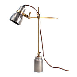Singer Table Lamp - A quirky source of task lighting with a delightful vintage theatrical look, the Singer Table Lamp spotlights your desktop with a gunmetal fixture on brass oxide arms that stand in a functional cylindrical base.  The visible hardware enhances the old-fashioned impression of a lamp inspired by the great artists' studios of the mid-century.  Perfect beside a drafting table, this table lamp has equal appeal illuminating a cozy reading chair or hearthside bench.