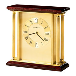 """Howard Miller - Howard Miller - Carlton Table Top Clock - Get the buzz on the hour in a classic contemporary style. Brass columns frame the base and the centerpiece. Slip into a timeless sense of fashion when wood combines with fine brass. Perfect atop of a mantel, desk, bedside or any table top selection. * Four solid brass reeded columns. . The brushed brass finished dial offers a circular spun numeral ring with diamond cut edges and black Roman numerals. . Full felt bottom protects your desktop. . Finished in Rosewood Hall on select hardwoods and veneers. . Quartz movement includes battery. . H. 8-3/4"""" (22 cm). W. 9"""" (23 cm). D. 3-3/4"""" (10 cm)"""