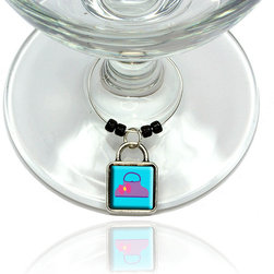 """Made on Terra - Purse Bag Handbag Shopping Light Purple Wine Glass Silver Charm - Your guests have arrived and the atmosphere is electric. A sip of wine here, a sip of a cocktail there and you find the conversation turning to the charming baubles you've placed on the glasses, something special you chose for each of your eclectic guests. They love them and appreciate your thoughtfulness. You love them for their uniqueness and that no one forgets which glass they were using.  Choose from Made on Terra's many designs for the best party ever. Ring is 1"""" diameter; measures 2"""" from top of ring to bottom of charm. Made of metal and plastic. Sold individually."""