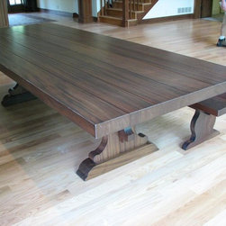 """Custom Dining Tables - This unique 4' x 10' Barcelona style table is constructed entirely of solid flat cut African mahogany hardwoods. The top is a full 3"""" thick with a slight distress finish and plank appearance. The table base is very unique, as it has a wedge joint at the stringer passing through the table base. This wedge is hammered into place with a mallet to tighten the joinery of the table…..this method dates back centuries in European furniture."""