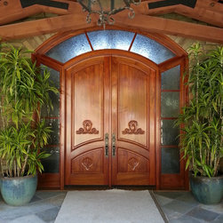 Rancho Santa Fe Mediterranean - A custom wood entry system in mahogany, featuring hand-carved panels and a decorative glass surround.