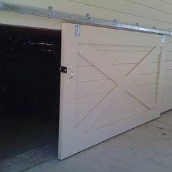 Doors - Custom Barn Door for an under floor storage area.  Hand built by our Craftsman and installed by our team.  Notice how the grooves in the door align with the siding of the house.  Attention to detail makes all the difference..