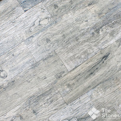 Magique Patina Gris Wood Plank Porcelain Tile - The gorgeous grey color of the wood planks is complimented by undertones of cream, blue and charcoal, creating a stunning patina effect that adds character and depth throughout the entire cabin. The simulated knots in the wood plank give the porcelain tile an authentic wood look that brings nature indoors without the extensive upkeep. Once you find your bed, you take a seat and breathe in the lovely decor around you; you're sure it's going to be a perfectly wonderful week.