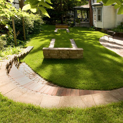 Spend an Afternoon Playing Horseshoes - Seating on the retaining walls, more seating on two patios off to the right and steps to a shady front porch maximizes the small space for entertaining.
