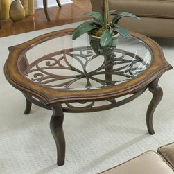 Riverside Furniture - Serena Round Cocktail Table in Brown Sugar Fi - Decorative metal motif suspended under top. Gracefully arched resin legs. Base levelers in bottom of legs. Tempered glass insert. CPSC HR-4040 certified. Made from hardwood solid and glass. 38 in. Dia. x 20 in. H (57 lbs.). Assembly Instructions