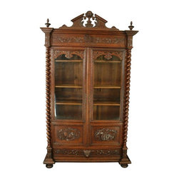 Used Antique Carved Oak French Renaissance Bookcase - The striking size and heavy carving on this antique oak French Renaissance bookcase ensure it will be the perfect focal point in any space. The art and music motifs make this Renaissance style display cabinet a particularly ideal choice in the music room or home library.    Original glass doors protect collections, while the nearly five-foot-wide bottom drawer offers countless options for use.    Overall Condition is Used - Very Good. Shows normal wear to the finish and wood separation on both sides, and to the decorative panel across the top due to age and use.