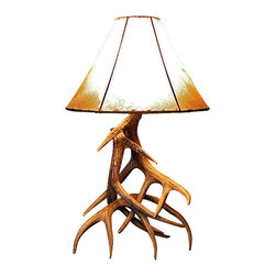 Muskoka Lifestyle Products - Whitetail Deer Three Antler Table Lamp - The Whitetail Deer Three Antler Table Lamp is the perfect solution for adding the right amount of cozy lighting and rustic atmosphere in small areas. The shade is a rawhide, which allows the light to penetrate with a warm glow while adding the perfect texture to this piece. Real antlers are used to model the reproduction for an exact and comparable result. The process to create our antler chandeliers uses a time proven, cast resin system to ensure perfection in every piece. We use the same process for our rustic western decor and accent lights. We have hand-stained and antiqued each antler to achieve the exact comparable match to the real antler. Bring the perfect rustic decor to your home, cabin, or office with these authentic antler reproductions.All lamps are UL listed to ensure absolute safety, quality, and US building code parameters are met.