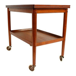 "Pre-owned Grete Jalk Danish Modern Teak Bar Serving Cart - Are you looking for the perfect Mid-Century bar cart for a small space? Well, you have Danish modern craftsmanship to thank for this understated yet functional convertible cart. Crafted of solid teak, with a hinged fold out table, it functions as a bar cart, serving cart, or extra space for your dining table. This piece is marked, ""Made in Denmark,"" and was designed by Grete Jalk. The cart is in good condition with minor age appropriate wear including a nick on the underside edge of the bottom shelf.     Table open length: 36.5"""