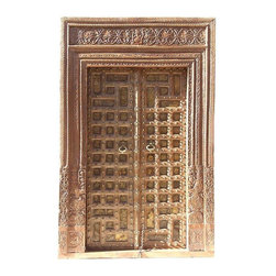 Used Antique Palace Entrance Door - A stunningly ornate 18th-century hand carved door that features floral patterns carved in a geometric pattern and inlaid with brass. It's adorned with beautiful wooden carved Toran (wooden carved lotus flowers with Ganesha in the center, believed to bring positive energy). It has the original brass knockers and brass stud details. This exquisite door comes in three pieces; two door panels and the frame. An incredible and rare royal piece.