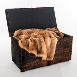 Cowhide covered storage ottoman furniture - A lovely leather storage box covered in cowhide. Use this furniture at the end of a bed or against a wall to store winter blankets. This storage ottoman is shown with a possum fur blanket.