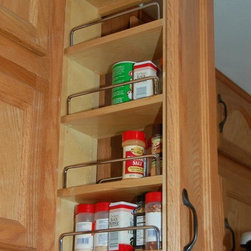 Pull Out Spice Rack - A narrow cabinet is ideal for a pull out spice rack.  We use the existing cabinet door for a seamless look from the exterior.  Our pull out shelves are all custom made to fit your cabinets.