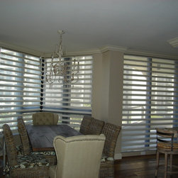 Window Treatments for Sliding Doors - Pirouette window shadings from Hunter Douglas add both beauty and function for this west facing condo.  Made with a room dimming fabric for sun and heat protection, these Pirouettes provide filtered light, light blocking or can be rolled up for a clear window.  This installation had the Hunter Douglas PowerRise battery operated motorization for ease of use