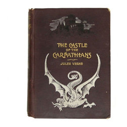 "Pre-owned Castle of the Carpathians Book by Jules Verne - Give your cocktail table or library collection some spooky flair with this very rare edition of Jules Verne's ""The Castle of the Carpathians."" It is the first American edition, which was published in 1894 (but this copy is undated) and is bound in maroon cloth decorated in black and white to set the mood for a mysterious tale. It is 211 pages of text with 38 beautiful (maybe creepy is a more fitting adjective, here) illustrations. This narrative is set in the area which in just a few years would become known as Dracula's homeland. The descriptions of the quaint villagers of Werst, their costumes, manner of living, and belief in the supernatural world would in themselves prove an interesting narrative, but when coupled with the exciting adventures of Nic Deck, the two Counts, the cowardly Doctor, and the beautiful La Stilla, the story is undoubtedly one of the most enchanting ever told.    It is shelf-worn, with some loss to the top and bottom of the spine and the binding is somewhat shaken, with two inside illustration pages detached. The previous owners name in pencil on front endpaper."