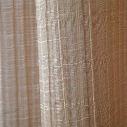 Wavy Sheer Drapery Fabric in Blush - Wavy Sheer Drapery Fabric in Blush is a rippled texture, neutral fabric that's perfect for draperies, curtains, or canopies. The understated stripe creates dimension, while the neutral colorway makes it easy to incorporate into existing designs. Made from 100% polyester, this fabric passes NFPA 701 fire rating. Width: 102″