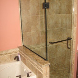 Framless Return Shower Doors with Knee Walls - Shower door is hinged off of the glass and off of the tiled wall. The glass-to-glass hinge is a 90 degree hinge with a knee wall adjustable hinge on the bottom. This door has a pull handle with towel bar for added functionality.