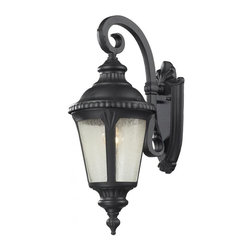 One Light Black Clear Seedy Glass Wall Lantern - Traditional and timeless, this small outdoor wall mount combines black cast aluminum hardware with seedy glass for a classic look.