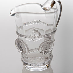 Lion's Head Pitcher - Small - Old-world charisma comes to your table with the Lion's Head Pitcher, a grand piece of clear glass drinkware that lends the authority and character of regal heraldry to the dining room, patio table, or home bar.  Made from weighty clear glass with bands of applied glass ornamentation and a hefty, comfortable handle, this smaller version of the Lions Head Pitcher, like its larger size, is ornamented by the calm, regal visages of three-dimensional lions.