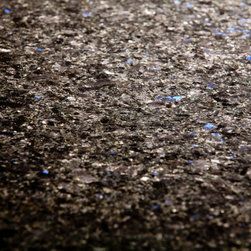 Blue in the Night Granite - Blue in the Night is a fascinating stone. It has subtle layers of black and grey in tight pattern. This gives it the edgy look of solid black without being as two dimensional as an Absolute Black Granite (and without the propensity for fingerprint mess). But what makes Blue in the Night Granite so utterly unique are the sparks of neon blue scattered throughout the stone that look like illuminated sapphires or blue stars in the night sky. This black granite has a fantastic polish and it's reflective quality picks up on any accent colors in the room. So if you add red to the room, you will see red in the stone etc. The edge profile is ogee edge in some places and half bullnose edge in others.  The circular table / island is a wonderful touch as well.