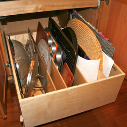 Base Cabinets and Other Creative Solutions - The pull out tray bin is a kitchen essential.  Organize cutting boards, cookie sheets, cake pans, platters, etc... in their own compartment.  Each item is easy to see, easy to retrieve, easy to put away.  What's not to like about the pull out tray bin?
