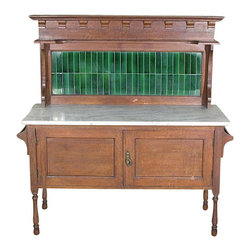 Antiques - Antique English Solid Oak Marbletop Vanity Washstand w/ Tiled Backsplash - This is a beautiful antique English solid oak marbletop vanity washstand. It features a beautiful marbletop that has a very attractive backsplash with lovely green tiles, a shelf on top and decorative accents. One corner of the tiles is slightly separated from the backsplash and the backsplash tends to lean backwards when pushed but it is in good condition as it is. In addition it has a cabinet that has 2 traditional paneled doors with an oval brass handle. The sides have 2 convenient hanging rods and it has attractive turned legs with casters.This piece may show minor age appropriate signs of wear including light discolorations, wood separations and small painted spotsbut as shown it is overall in very good cosmetic and structural condition and it is strong and sturdy.Other Dimensions (In inches): Top Surface 30.25H x 48W x 18.5D. Cabinet 15.25H x 43.25W x 15.5D.