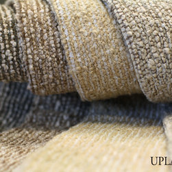 Upland - American woven Upland from Calvin Fabrics offers a nice boucle with a subtle horizontal strie effect for upholstery use. Soft grey River Rock features chenille in an icy grey to putty juxtaposed with cream boucle and mocha warp yarns. Warm sand boucle sets the tone for Sisal which features a white to vanilla chenille; depth of tone is enhanced by repetition of the same warm sand coloring in the warp yarns. Driftwood features both khaki chenille and warp yarns against cream boucle. Travertine employs a taupe to brown chenille, khaki warp yarns and cream boucle yarns.