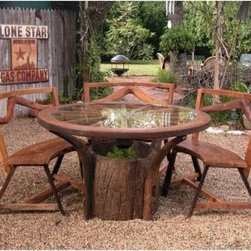 Jackson Hole Dining Table Set - Gather 'round the Jackson Hole Table for an afternoon of memorable merrymaking. Recall past times with old friends while sipping a cool drink or spin some fresh yarn with new folks. No matter the occasion the enjoyment rolls on. The tempered glass top stands strong against the harsh elements. Underneath the glass is an old-time wagon wheel. Resilient reclaimed teak wood comes of age with dignifying grace. Grow plants in the hollowed center stump. Each of the four benches in the Jackson Hole Dining Table Set measures 36L x 19W x 35H inches with a seat height of 19 inches.The Jackson Hole Table makes a living fixture in your indoor or outdoor decor.