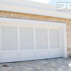 Neoclassic Custom Garage Door in Composite Wood Materials - This traditional style garage door was handcrafted out of eco-friendly composite wood materials painted with a high quality exterior paint grade finish. The garage door design consists of louver slats that were hand made individually and put together by hand. The bottom raised panels add some aesthetic weight right where its needed to balance out the gorgeous traditional door design. Adding molding around the perimeter of the lover panels and raised panels add dimension and a phenomenal finishing touch that played well with the home's lavish moldings and casings.