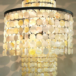 Jude Chandelier - A column draped in shell suspends an additional ring of larger pearly discs to create the Jude Chandelier. Its outline is traditional and festive, juxtaposing easy shapes that suit the form of average rooms, but its construction is more complex, with every carefully-cut circle of pale shell alive with soft sheen and gentle hue. Make your decor shimmer by crowning it with this light.