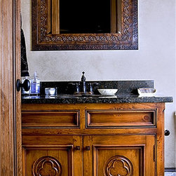 "Cover Photos - The hand built vanity with wood top is built with solid wood construction. Inset doors are 1-1/8"" thick with a antique finish on a stained wood.  The circles and clover is hand carved into the flat panels of the doors."