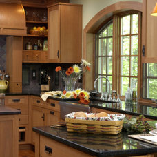 Sleek black countertops are an ideal contrast to light-colored maple cabinetry  