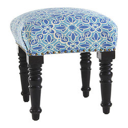 Casablanca Stool - The bold design on this ottoman was inspired by the many tile mosaics found throughout Casablanca, Morocco's largest city. It's a sophisticated look with turned, acacia wood legs and brass-studded trim. The story of Morocco is a colorful one, filled with traditions originating from Europe to China. Even today, the country is a vibrant melting pot of influences from mystical arts, music, and astrology. You'll see some of them reflected in this stool.