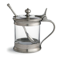 Tavola Jam Jar With Spoon - A refined update to a cafe-style server, the Tavola Jam Jar with Spoon is designed for hearty preserves at tea and breakfast, but its handle has a clip so that it can be used like a pitcher for thinner sauces. The jar is made from clear glass and accented with authentic Italian pewter that forms the handle, lid, and attractive shaped finial on this practical Italian tabletop piece.