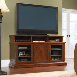 "Sauder - Arbor Gate 60.039"" TV Stand - Traditional motifs meet modern function in the Arbor Gate collection. Skillfully designed layers of beautiful detailing include panel doors with beaded frames, large crown moldings over plinth buttressing, frame and panel construction elements and contoured foundations. The thoughtful design and attention to detail extend to functional updates that incorporate contemporary technology solutions for flat panel televisions, computer monitors and laptop computers. The deep color and rich grain of Coach Cherry finish, combined with authentic pulls in an old-brass finish, carry a timeless patina that allows Arbor Gate to effortlessly blend tradition and technology into an ideal solution for modern day living. Features: -Holds TVs weighing up to 135 lbs or less; base must not be longer than 60 inches.-Pull-out laptop stand offers versatile functionality.-Four adjustable shelves behind framed, safety-tempered glass doors.-Cubbyhold storage.-Coach Cherry finish.-Arbor Gate collection.-Recommended TV Type: Flat.-TV Size Accommodated: 60"".-Finish: Coach Cherry.-Powder Coated Finish: No.-Gloss Finish: No.-Material: Engineered wood.-Number of Items Included: 2 items; credenza and pull-out laptop stand.-Solid Wood Construction: No.-Distressed: No.-Exterior Shelves: Yes.-Drawers: No.-Cabinets: Yes -Number of Cabinets: 3.-Number of Doors: 3.-Door Attachment Detail: Hinges.-Interchangeable Panels: No.-Magnetic Door Catches: Yes.-Cabinet Handle Design: Knobs.-Number of Interior Shelves: 9.-Adjustable Interior Shelves: Yes..-Scratch Resistant: No.-Removable Back Panel: No.-Hardware Finish: Dark brown metal.-Casters: No.-Accommodates Fireplace: No.-Lighted: No.-Media Player Storage: Yes.-Media Storage: Yes.-Cable Management: Cable hole.-Remote Control Included: No.-Weight Capacity: 135 lbs.-Swatch Available: Yes.-Commercial Use: No.-Collection: Arbor Gate.-Eco-Friendly: Yes.-Recycled Content: No.-Lift Mechanism: No.-Expandable: No.-TV Swivel Base: No.-Integrated Flat Screen Mount: No.-Non-Toxic: Yes.-Product Care: Wipe with a damp cloth.-Country of Manufacture: United States.Specifications: -ISTA 3A Certified: Yes.-CARB 2 Certified: Yes.-CARB Certified: Yes.-FSC Certified: Yes.-General Conformity Certified: Yes.-EPP Certified: Yes.Dimensions: -Overall Height - Top to Bottom: 32.913"".-Overall Width - Side to Side: 60.039"".-Overall Depth - Front to Back: 20.315"".-Drawer: No.-Shelving: Yes.-Cabinet: Yes.-Legs: Yes.-Overall Product Weight: 176 lbs.Assembly: -Assembly Required: Yes.-Tools Needed: Phillips screwdriver and hammer.-Additional Parts Required: No.Warranty: -Product Warranty: 5 Years."
