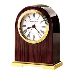 """Howard Miller - Howard Miller - Carter Table Top Clock - Tiered brass stablilizes this wonderful rosewood accented timepiece with golden finishes framing the circular centerpiece. Roman numerals send a sense of classicism to this piece while glossy finish finds a home in contemporary styles. * Polished brass finished base. . A polished brass tone bezel frames the white dial with black numerals. . Full felt bottom protects your desktop. . Finished in Rosewood Hall on select hardwoods and veneers. . Quartz movement includes battery. . H. 6-1/2"""" (17 cm). W. 4-3/4"""" (12 cm). D. 2-1/2"""" (6 cm)"""
