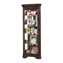 """Howard Miller - Constance Hampton Cherry Corner Curio Cabinet - Elegant Hampton Cherry corner cabinet offers intricate detailing with top floral overlay and bottom rosettes to provide a beautiful frame for your fine collectibles. Five levels of display space, with four adjustable glass shelves include Pad-Lock�� cushioned metal shelf clips to increase stability and safety. Additional conveniences include No-Reach�� light switch located discretely on the cabinet back. * This handsome corner cabinet will turn an empty corner into a smart display space. Highlights and glazing enhance the Hampton Cherry finish. . An intricate floral overlay decorates the top, and complementing decorative rosettes accent the lower door. . Five levels of display space with four glass shelves offer ample space for your collection. . Lightly distressed finish in Hampton Cherry on select hardwoods and veneers. . Adjustable levelers under each corner provide stability on uneven and carpeted floors. . Pad-LockT cushioned metal shelf clips increase stability and safety. . Cabinet is illuminated by an interior light. . Glass shelves can be adjusted to any level within your cabinet. . Glass mirrored back beautifully showcases your collectibles. . No-ReachT light switch is conveniently located on the back of the cabinet.. H. 72"""" (183 cm). W. 28"""" (71 cm). D. 16"""" (41 cm)"""