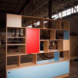 Entry bookcase - A custom entry way bookcase that also serves as a room divider by Kerf Design made with maple Europly (a birch core plywood available with maple or walnut veneer) and Abet Laminati laminate in poppy red and space blue.