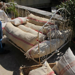 Hemp grain sacks made into pillows in Provence - Vintage hemp grain sacks have been made into pillows by sewing tape or ribbon to the ends and tying...
