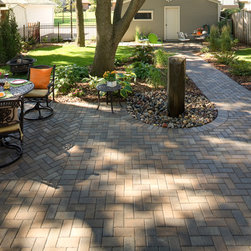 Best Use of Backyard Space - The paver patio wraps around this tree which is the focal point of the yard.  The patio runs the length of the yard, leading to the garage. Note the paver inlay which defines the dining area of the patio.